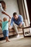 Усмехаться parents помогать их младенцу сделать первые шаги в их стоковое изображение