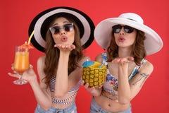 Усмехающся 2 женщины выпивая коктеили дуя поцелуи Стоковое Фото