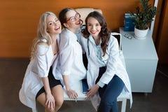 Усмехающся 3 доктора сидя на таблице в шкафе Стоковое фото RF