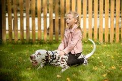 Усмехающся, поя маленькая девочка обнимая большую собаку в луге, играх внешних Счастливый ребенок любит ее любимчика Положительно стоковое изображение rf