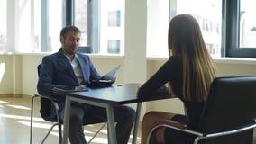 Усмехающся работодатель спрашивает вопросы к женщине в интервью сток-видео