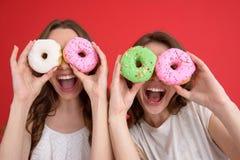 Усмехающся 2 друз дам стоя с donuts Стоковые Фотографии RF