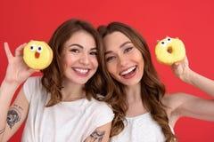 Усмехающся 2 друз дам стоя с donuts Стоковое Фото