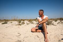Усмехаясь авантюрист, как современный дикарь, сидит на дезертированном море стоковые фотографии rf