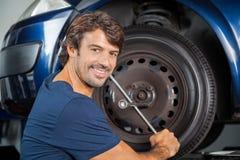Усмехаясь автошина автомобиля отладки механика с ключем оправы Стоковая Фотография