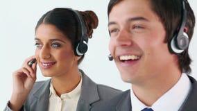 Усмехаясь агенты центра телефонного обслуживания используя шлемофоны видеоматериал