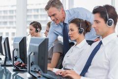 Усмехаясь агент центра телефонного обслуживания порции менеджера Стоковое фото RF