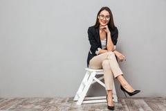Усмехаясь азиатская бизнес-леди в eyeglasses сидя на стуле Стоковые Фото