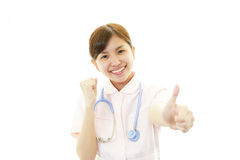 Усмехаясь азиатская женская медсестра с большими пальцами руки вверх Стоковое Изображение