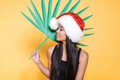 усмехаясь азиатская женщина в черном купальнике и шляпе santa держа поддельную ладонь стоковое фото rf