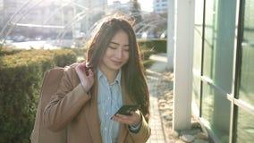 Усмехаясь азиатская женщина отправляя СМС на smartphone внешнем акции видеоматериалы