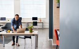 Усмехаясь азиатская дизайнерская склонность на его столе используя компьтер-книжку Стоковые Фото