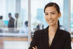 Усмехаясь азиатская коммерсантка в офисе стоковые фотографии rf