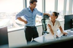 Усмехаясь азиатская коммерсантка с мужским коллегой на ее столе Стоковое фото RF
