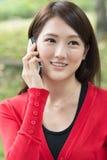 Усмехаясь азиатская молодая женщина принимает звонок стоковые фото