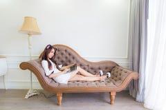 Усмехаясь азиатская молодая сексуальная женщина используя компьтер-книжку пока ослабляющ дальше так стоковая фотография rf