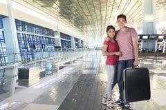 Усмехаясь азиатская пара держа багаж кладет в мешки к путешествовать Стоковое Изображение