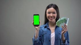 Усмехаясь азиатские смартфон удерживания женщины и евро, работа онлайн, получают наличными назад акции видеоматериалы