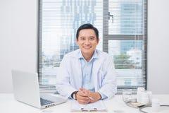 Усмехаясь азиатский доктор сидя на его столе в медицинском офисе Стоковое Изображение RF