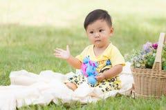Усмехаясь азиатский малыш мальчика сидит на белом хлопке в зеленых gras Стоковые Изображения
