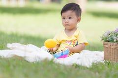 Усмехаясь азиатский малыш мальчика сидит на белом хлопке в зеленых gras Стоковое Изображение