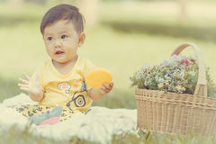 Усмехаясь азиатский малыш мальчика сидит на белом хлопке в зеленых gras Стоковое Фото