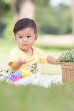 Усмехаясь азиатский малыш мальчика сидит на белом хлопке в зеленых gras Стоковое фото RF