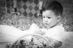 Усмехаясь азиатский малыш мальчика сидит на белом хлопке в зеленых gras Стоковые Фото