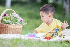 Усмехаясь азиатский малыш мальчика сидит на белом хлопке в зеленых gras Стоковые Изображения RF