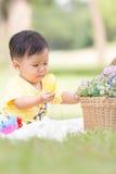 Усмехаясь азиатский малыш мальчика сидит на белом хлопке в зеленых gras Стоковые Фотографии RF