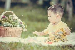 Усмехаясь азиатский малыш мальчика сидит на белом хлопке в зеленых gras Стоковая Фотография RF