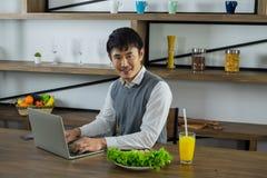Усмехаясь азиатский молодой бизнесмен и здоровый стоковое фото