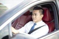 Усмехаясь азиатский молодой бизнесмен управляя автомобилем стоковая фотография