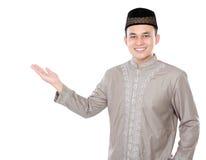 Усмехаясь азиатский мусульманский человек представляя космос экземпляра стоковое изображение