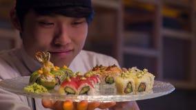 Усмехаясь азиатский шеф-повар в белой форме стоя внутри акции видеоматериалы