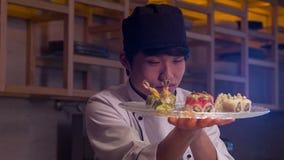 Усмехаясь азиатский шеф-повар в белой форме стоя внутри видеоматериал
