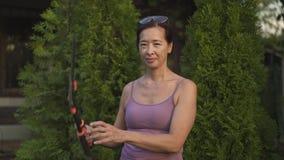 Усмехаясь азиатское положение женщины с ножницами в ее саде акции видеоматериалы