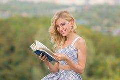 Усмехаясь дама с книгой outdoors Стоковое Фото