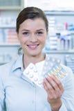 Усмехаясь аптекарь показывая медицину в фармации Стоковые Изображения RF