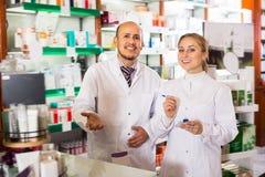 2 усмехаясь аптекаря стоя рядом с полками Стоковая Фотография RF