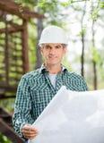 Усмехаясь архитектор держа светокопию на месте Стоковое Изображение