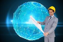 Усмехаясь архитектор при трудная шляпа смотря планы Стоковое Изображение