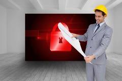 Усмехаясь архитектор при трудная шляпа смотря планы Стоковая Фотография RF