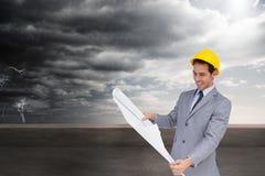Усмехаясь архитектор при трудная шляпа смотря планы Стоковая Фотография