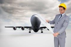 Усмехаясь архитектор при трудная шляпа смотря планы Стоковые Фото
