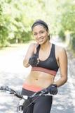 Усмехаясь атлетическая красивая латинская женщина с велосипедом, здоровым lif стоковая фотография rf