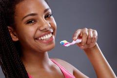 Усмехаясь африканская девушка с зубной щеткой, концом вверх Стоковое Изображение RF