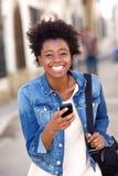 Усмехаясь африканская женщина идя снаружи с сотовым телефоном Стоковая Фотография