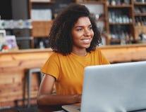 Усмехаясь африканская женщина с ноутбуком в кафе стоковые изображения rf