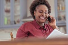 Усмехаясь африканская обработка документов чтения женщины и говорить на ее мобильном телефоне Стоковое Изображение RF